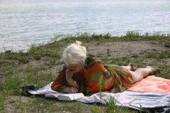 Die Frau, die einen Rest nahe Wasser hat stockfotografie