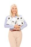 Die Frau, die einen Stapel des Toilettenpapiers hält, rollt Stockfoto
