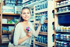 Die Frau, die Farbe im Aerosol kann im Shop wählt Lizenzfreies Stockbild