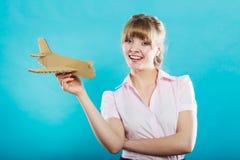 Die Frau, die an Ferien denkt, hält Flugzeug Stockfotografie