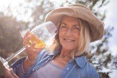 Die Frau, die Glas Wein in den Oliven betrachtet, bewirtschaften Stockbilder
