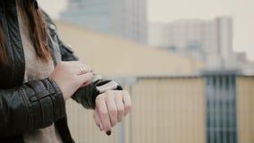 Die Frau, die ihr smartwatch mit Berührungseingabe Bildschirm steht auf dem Dach verwendet, geht dann weg übergibt Nahaufnahme 4K Lizenzfreies Stockbild