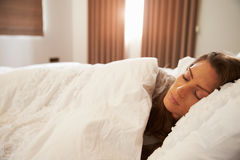 Die Frau, die im Bett als Sonnenlicht schlafend ist, kommt durch Vorhänge Stockbild