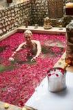 Die Frau, die im Blumen-Blumenblatt sich entspannt, bedeckte Pool am Badekurort Lizenzfreie Stockfotos