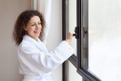 Die Frau, die im weißen Bademantel gekleidet wird, öffnet Fenster Lizenzfreie Stockfotografie