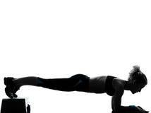 Die Frau, die Jobstepp Aerobics ausübt, drücken ups Lizenzfreie Stockbilder