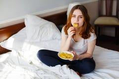 die Frau, die Kartoffelchips im Betthaus isst, erschrak die Gewinnung des Gewichts Lizenzfreie Stockfotos