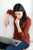 Die Frau, die an Laptop arbeitet und denkt Lizenzfreies Stockfoto