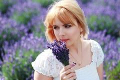 Die Frau, die am Lavendelfeldgriff sitzt, blüht in der Hand Stockfotografie