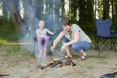 Die Frau, die Lebensmittel, die Leute kampieren im Wald, Familie Active in der Natur kocht, zünden Feuer, Sommersaison an Stockbild