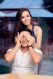 Die Frau, die Man's bedeckt, mustert, ihn auf einem Blind-Date überraschend Lizenzfreie Stockbilder