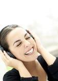 Die Frau, die mit Augen lächelt, die Kopfhörer schloss und trägt Lizenzfreie Stockbilder