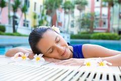 Die Frau, die mit Augen sich entspannt, schloss durch die Seite des Swimmingpools, Blumen im Haar Lizenzfreies Stockbild