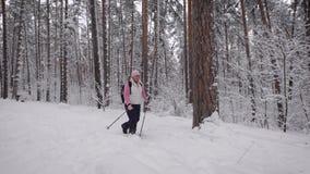 Die Frau, die mit einem schwarzen Rucksack auf Schultern gealtert wird, geht Fußweg des Winterwaldes, den die älteren Personen he stock video footage