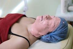 Die Frau, die mit liegt, ziehen weg Gesichtsmaske ab Lizenzfreie Stockfotos