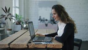 Die Frau, die Mitteilung durch Handy sendet und durch Laptop arbeitet stock footage