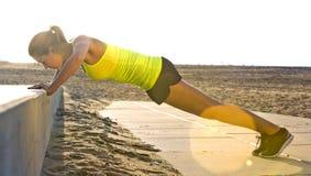 Die Frau, die Presse tut, ups auf einen Strand Lizenzfreie Stockfotos