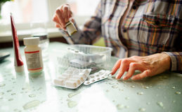Die Frau, die rheumatoide Arthritis hat, nimmt Medizin ein Stockfotografie