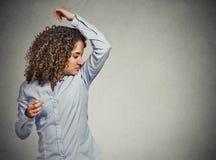 Die Frau, die riecht, schnüffelnd ihre Achselhöhle etwas, stinkt Lizenzfreie Stockfotos