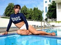 Die Frau, die sexy Badeanzug trägt, sitzt am Rand eines Pools Lizenzfreie Stockfotografie