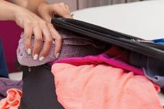 Die Frau, die sie verpackt, machen mit Kleidung weiter Stockbilder
