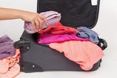 Die Frau, die sie verpackt, machen mit Kleidung weiter Stockfotografie