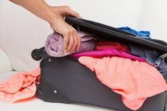 Die Frau, die sie verpackt, machen mit Kleidung weiter Lizenzfreie Stockbilder