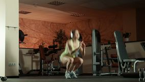 Die Frau, die Sportübung tut, hockt und springt
