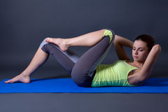 Die Frau, die Stärke tut, trainiert für Bauchmuskeln über Grau Stockbild