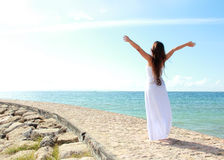 Die Frau, die am Strand mit den Armen sich entspannt, öffnen das Genießen ihrer Freiheit