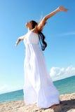 Die Frau, die am Strand mit den Armen sich entspannt, öffnen das Genießen ihrer Freiheit Stockbilder