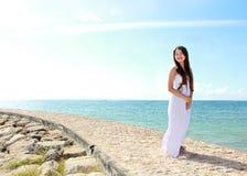 Die Frau, die am Strand mit den Armen sich entspannt, öffnen das Genießen ihrer Freiheit Stockfotografie