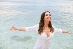 Die Frau, die am Strand mit den Armen sich entspannt, öffnen das Genießen ihrer Freiheit Stockbild