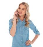 Die Frau, die am Telefon spricht, schaut, um mit Seiten zu versehen Lizenzfreie Stockfotos
