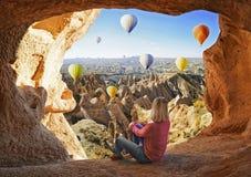 Die Frau, die wie bunte Heißluft aufpasst, steigt das Fliegen über das Tal bei Cappadocia im Ballon auf stockfotografie