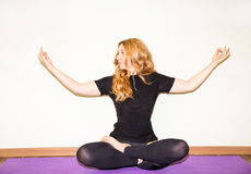Die Frau, die Yoga tut, trainiert und pilates wirft auf Matte auf weißem Hintergrund auf Asana Das Konzept des Sports, der Eignun Stockbilder