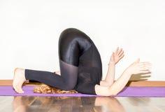 Die Frau, die Yoga tut, trainiert und pilates wirft auf Matte auf weißem Hintergrund auf Asana Das Konzept des Sports, der Eignun Lizenzfreie Stockbilder
