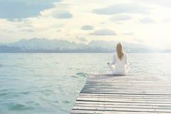 Die Frau, die Yoga tut, trainiert vor einer großartigen Landschaft lizenzfreies stockbild