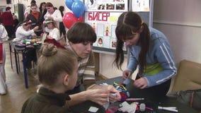 Die Frau, die zwei Mädchen hilft, stellen weiche handgemachte Puppen bei Tisch her festival kreation teens stock video footage