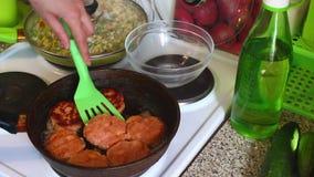 Die Frau dreht die Koteletts vom Lachsfleisch, die in einer Bratpfanne gebraten werden stock footage