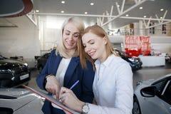Die Frau, die eine AutoVersicherungspolice, das Mittel unterzeichnet, zeigt auf das Dokument stockfotografie