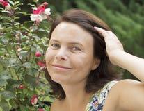 Die Frau in einem Garten. Stockfotos