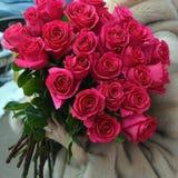 Die Frau in einem Pelzmantel mit einem enormen Blumenstrauß von Rosen lizenzfreie stockfotografie
