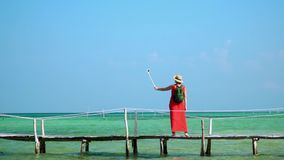 Die Frau in einem roten Kleid geht auf einen Pier mit einem grünen Rucksack Der Reisende fotografiert sich auf Selfie-Stock auf a stock video footage