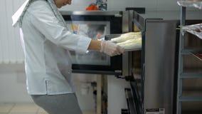 Die Frau in einem Süßwarenladen Das Mädchen in einer weißen Form und farblosen in einer Handschuh- und Grauenhose hat Teig auf a  stock footage