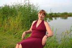Die Frau in einem Sommerrotweinkleid sitzt auf der Bank des Sees Lizenzfreie Stockbilder