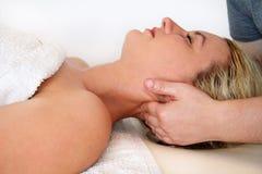 Die Frau, die einen Massagehals nimmt, mischt am Massagetisch mit lizenzfreie stockfotografie