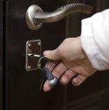 Die Frau öffnet die Tür mit einem Schlüssel Stockfotografie
