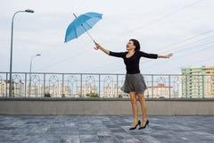 Die Frau fliegt mit einem Regenschirm Stockfoto