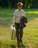 Die Frau, gealtert mit einem Koffer in ihrer Hand, geht entlang den ro Lizenzfreie Stockfotografie